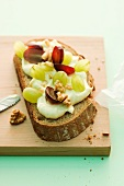 A slice of bread topped with cream cheese butter, grapes and nuts