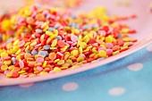 Bunte Zuckerstreusel auf Teller (Nahaufnahme)