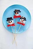 Drei Cake Pops (Minikuchen am Stiel) in Schneemannform