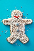 A gingerbread man decorated with chocolate beans and icing sugar