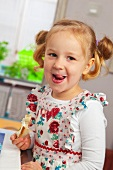 Little girl eating bread with cottage cheese and cress