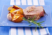 A slice of turkey roulade with rosemary and a side of vegetables