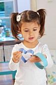 A little girl holding cutters