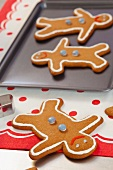 Gingerbread men on a table and a baking tray