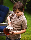 A boy pouring juice into a glass