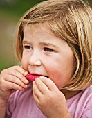 A girl eating a radish
