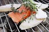 A salmon fillet and slices of bread on a barbecue with bunches of herbs