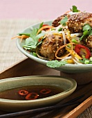 Chicken fritters with sesame seeds on vegetables (Asia)