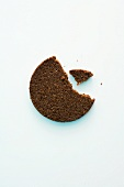 A slice of pumpernickel bread with a bite taken out