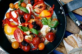 Fried eggs with tomatoes, olives and basil in a pan