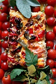 A slice of pizza with tomatoes, coppa and artichokes