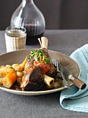Lamb Shank with Vegetables and a Decanter of Red Wine