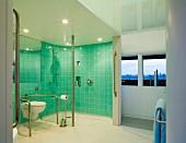 Grossräumiges Bad mit türkisen Wandfliesen im WC- und Duschbereich