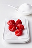 Fresh raspberries on a serving platter with cream