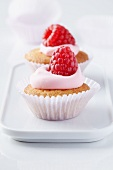 Mini muffins topped with raspberry mousse and fresh raspberries