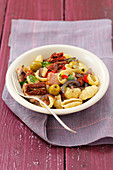 Shell pasta with ham, olives and dried tomatoes
