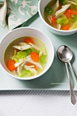 Two Bowls of Chicken Soup on a Tray with Two Spoons