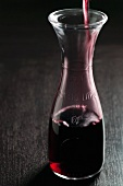 Red Wine Pouring into a Half Carafe