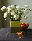 White Ranuncula Arrangement in a Square Vase; Mandarin Oranges