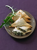 Spanakopita Triangles on a Plate on a Purple Table Cloth
