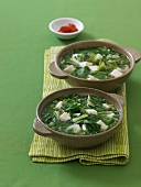 Two Bowls of Tofu and Greens Soup on a Green Napkin