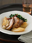 Pork Slices with Apples, Garlic and Greens in a White Plate