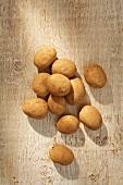 Mehrere Kartoffeln auf Holzuntergrund (Aufsicht)