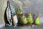 An enamel plate and pears in a wire basket