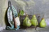 Emaillie-Teller und Birnen in einem Drahtkorb