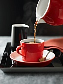 Hot Coffee Pouring From a Red Coffee Pot into a Red Coffee Cup