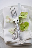 Place setting with silver cutlery on linen napkin and hydrangea florets