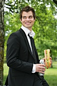 Young man with baguette sandwich and water in park