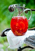 Punch with summer fruits in a pitcher on a garden chair