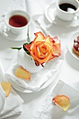 A rose, tea and coffee on a breakfast tables set in white