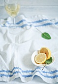 Fresh lemon, sage and a glass of white wine on a kitchen towel