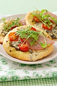 Mini pizzas with ham, blue cheese, rocket and cherry tomatoes