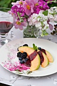 Melon with blackberry and blueberry sauce