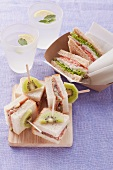 Whole wheat sandwich with tuna fish and finger sandwiches with Parma ham and kiwi