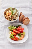 Carrot-apple salad with wild garlic cheese and tomato salad with peaches and mozzarella