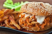 Shredded Buffalo Chicken Sandwich on a Sesame Seed Roll with French Fries