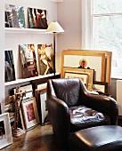 Gemütlicher Ledersessel mit passendem Fussschemel vor Regal mit aufgestellten Bildern