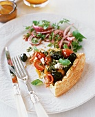 A slice of ricotta, black olive, cherry tomato and basil tart