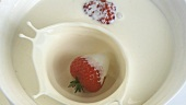 A strawberry falling into a bowl of cream
