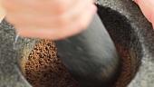 Crushing cumin in a mortar