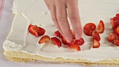 Arranging strawberries on sponge and cream base