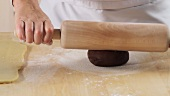 Dusting a worksurface with flour and rolling out dark shortbread dough