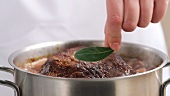 Adding a bay leaf to braised beef