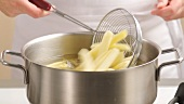 Placing chips in the deep-frying fat using a slotted spoon