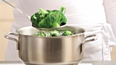 Removing cooked broccoli from a pan