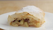 Dusting apple strudel with icing sugar